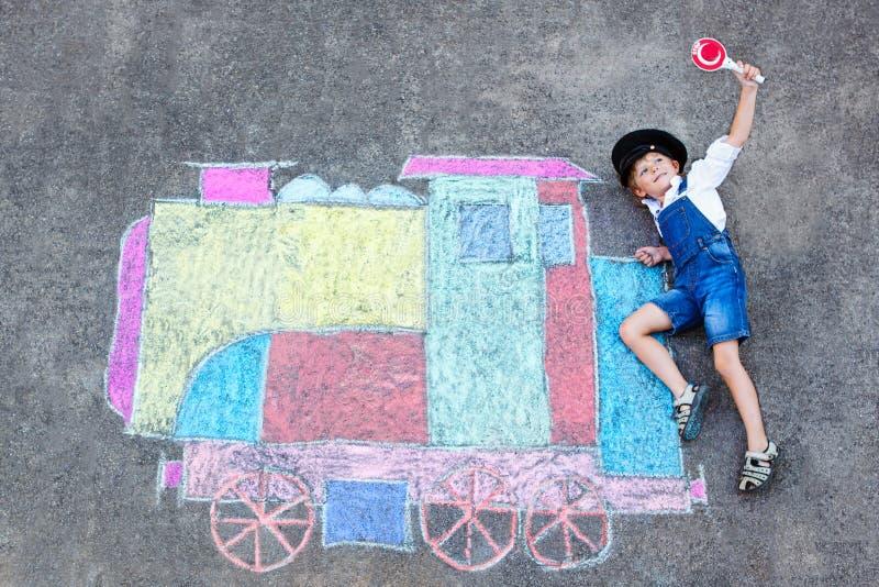 获得小孩的男孩与火车的乐趣用粉笔写图片 免版税图库摄影
