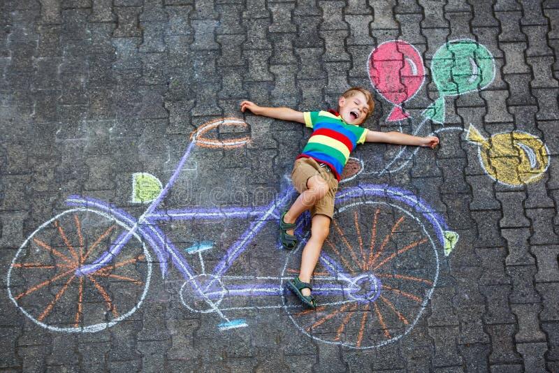 获得小孩的男孩与自行车的乐趣用粉笔写图片 免版税图库摄影