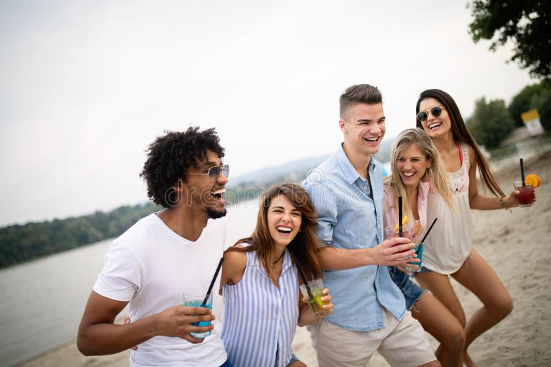 获得小组的朋友享受海滩假期和乐趣 免版税库存照片