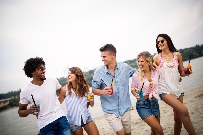 获得小组的朋友在海滩的乐趣 夏天休假、假期和人概念 库存图片