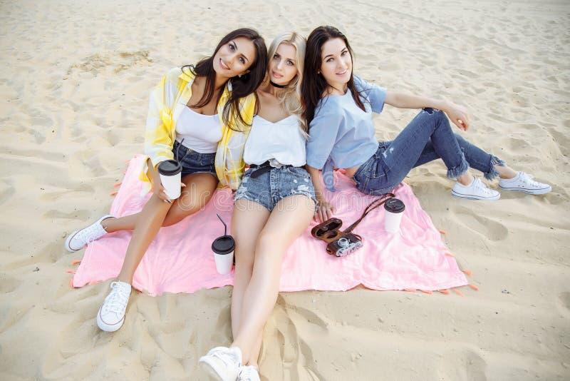 获得小组的朋友坐在海滩和乐趣 图库摄影