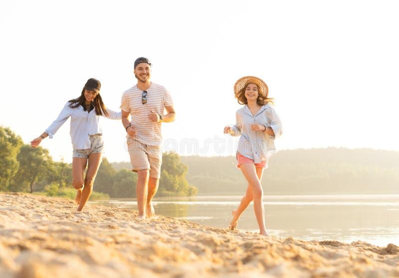 获得小组的朋友跑在海滩下的乐趣 库存照片