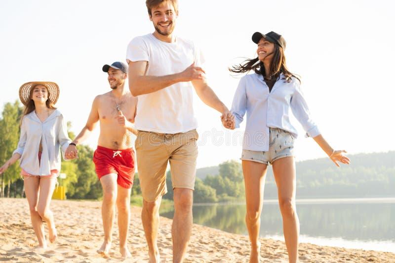 获得小组的朋友跑在海滩下的乐趣 免版税库存照片