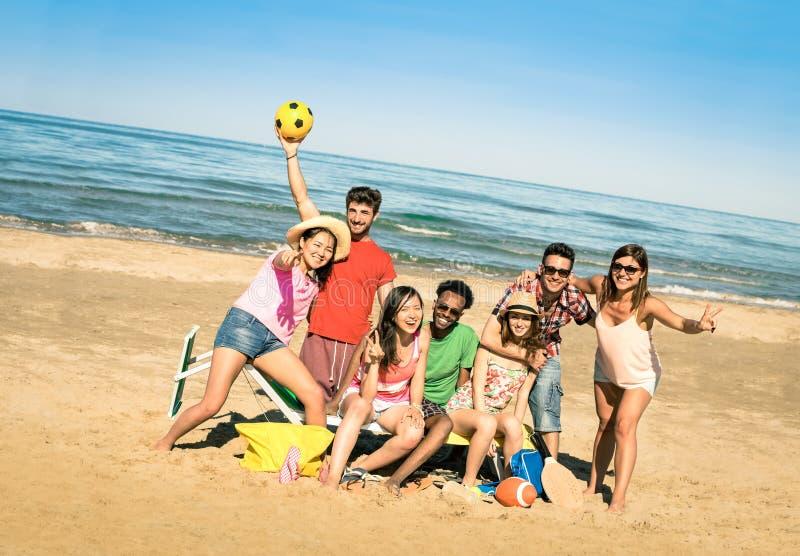 获得小组多种族愉快的朋友与海滩比赛的乐趣 图库摄影