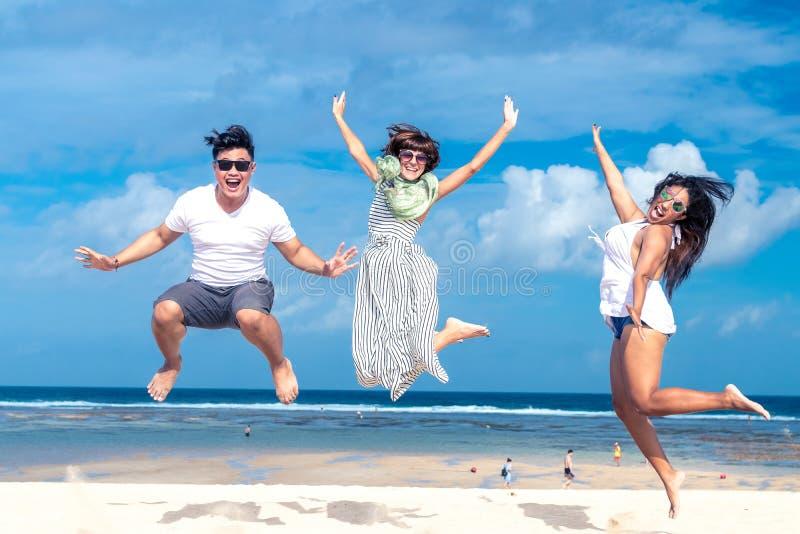 获得小组多种族的朋友在海滩的乐趣热带巴厘岛,印度尼西亚 库存图片