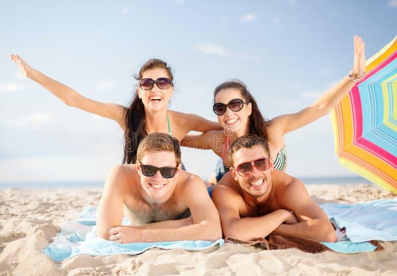 获得小组微笑的人民在海滩的乐趣 库存图片