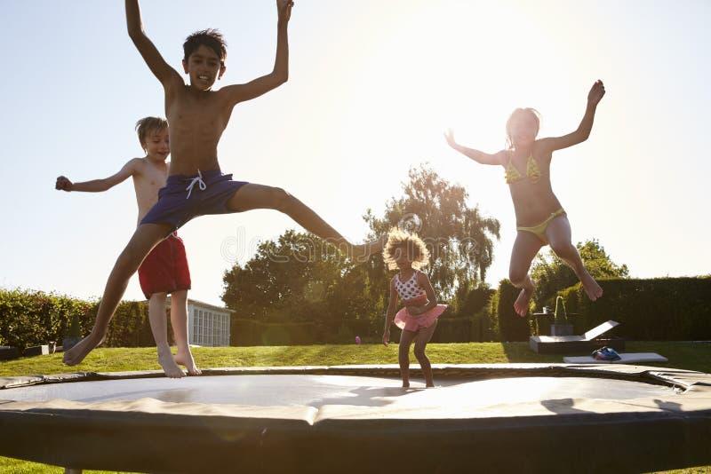 获得小组的孩子跳跃在室外绷床的乐趣 免版税库存照片