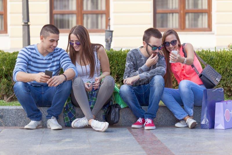 获得小组的朋友在城市街道上的乐趣 库存图片