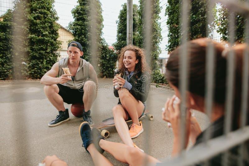 获得小组的朋友坐在篮球场和乐趣 免版税库存图片
