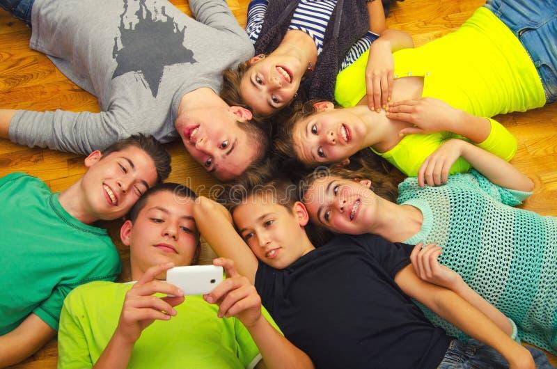 获得少年的朋友在地板上的乐趣 库存照片