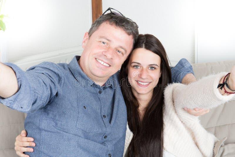 获得年轻愉快的人与他拍与手机的逗人喜爱的深色的女儿的乐趣selfie照片 免版税库存照片