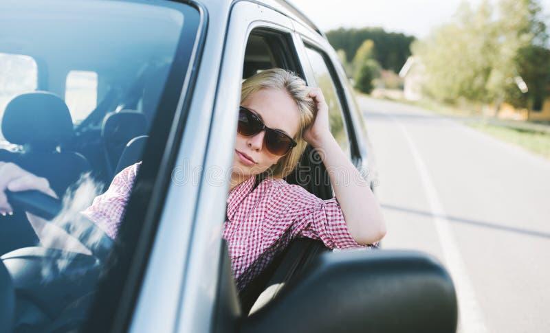 获得年轻白种人白肤金发的妇女旅行乘汽车和在她的夏天休假旅途上的乐趣 驾驶在乡下的愉快的女孩汽车 免版税库存图片