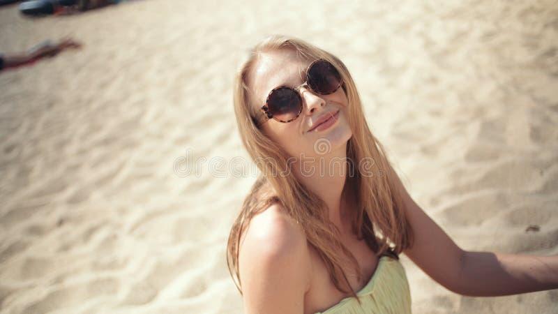 获得年轻白肤金发的妇女坐海滩和乐趣 库存图片