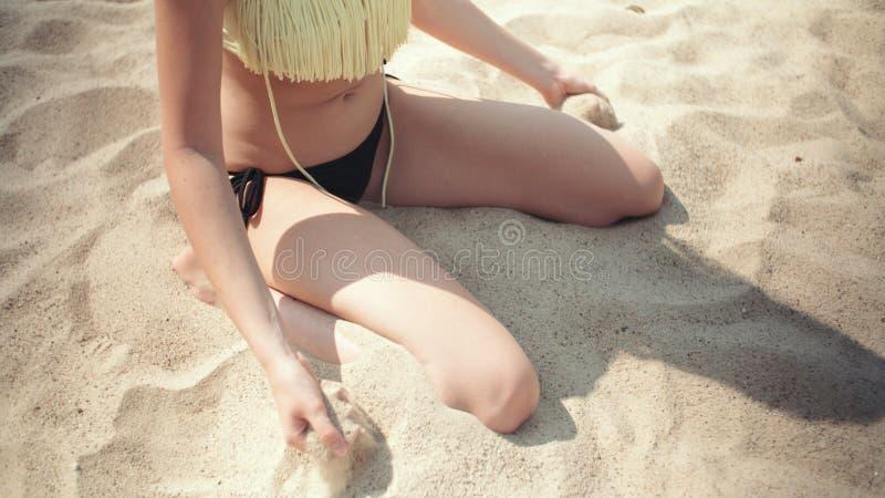 获得年轻白肤金发的妇女坐海滩和乐趣 免版税库存照片