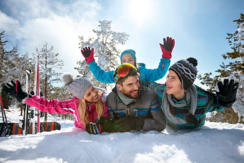 获得年轻的家庭在新鲜的雪的乐趣冬天假期 免版税库存图片