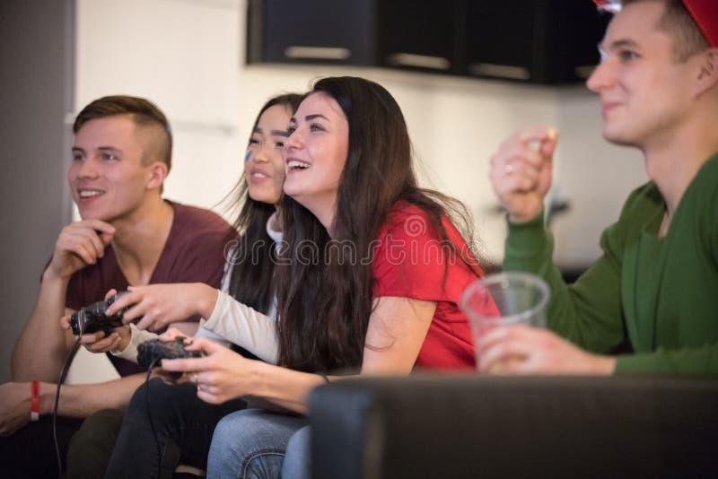 获得年轻的朋友公司乐趣一起 两打比赛的年轻女人使用控制杆 兴奋 库存照片