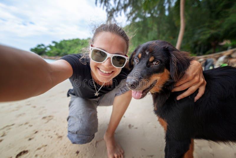 获得年轻美丽的愉快的快乐的女孩的妇女采取在一个手机的乐趣一selfie有她的在海滩的狗的沿沙子 免版税库存照片