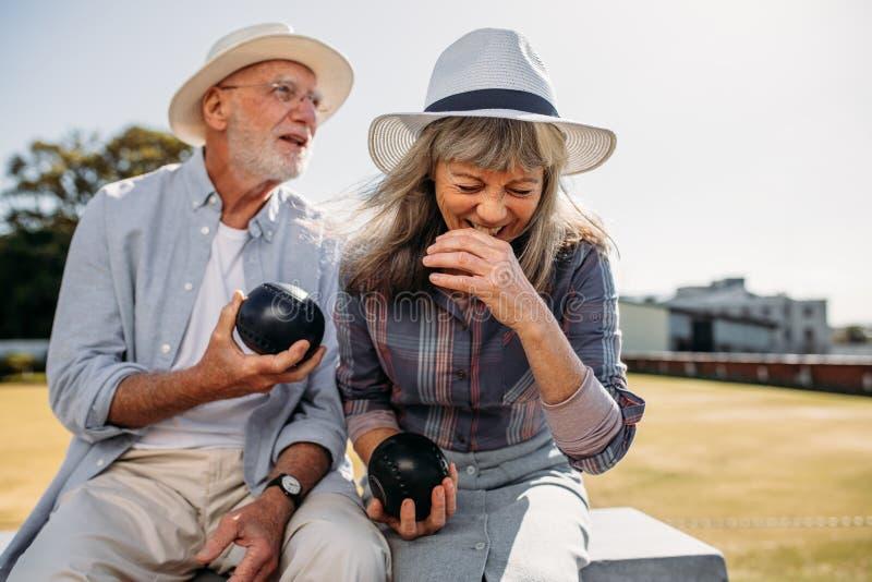 获得年长的夫妇坐在公园的乐趣举行议 免版税库存图片