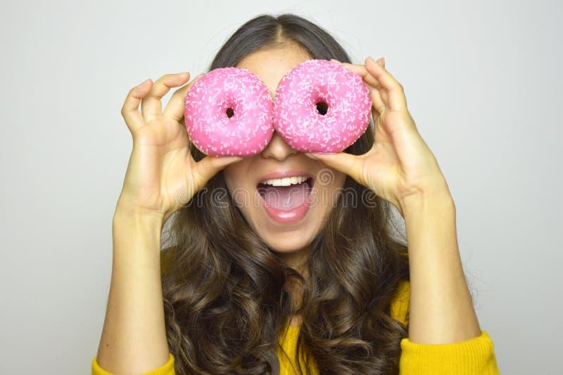 获得微笑的女孩与在灰色背景隔绝的甜点的乐趣 有摆在用多福饼的长的头发的可爱的少妇 免版税库存照片