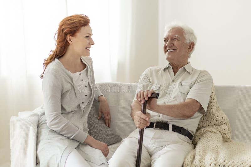 获得微笑的老人与愉快的女儿的乐趣在家 免版税库存照片
