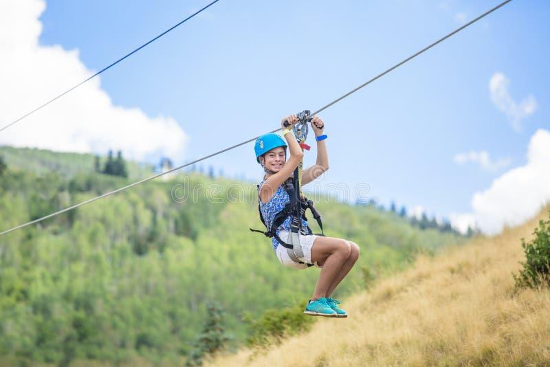 获得微笑的青少年的女孩乘坐zipline的乐趣乘坐 免版税库存照片