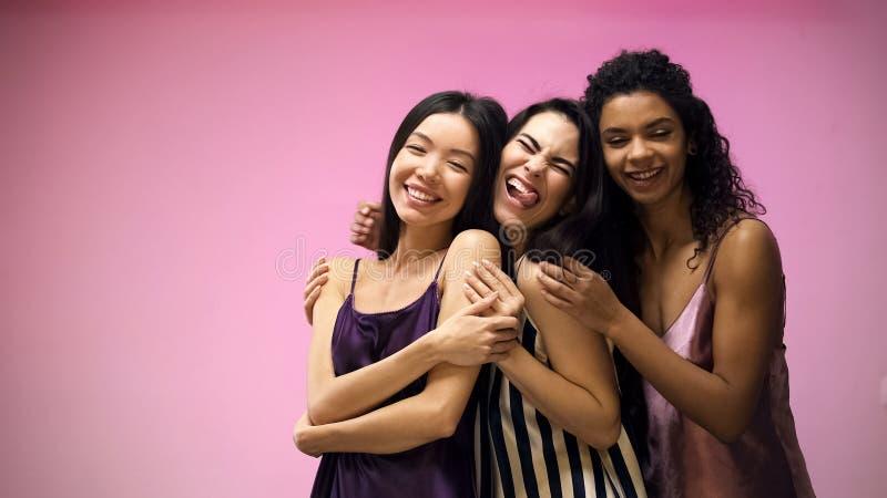 获得快乐的多种族的朋友摆在为照相机和乐趣,桃红色背景 免版税库存照片