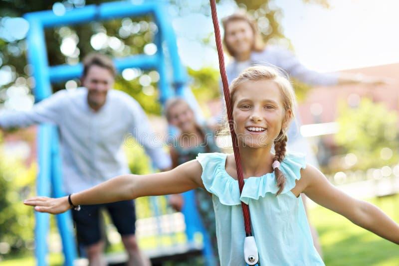 获得快乐的家庭在操场的乐趣 库存照片