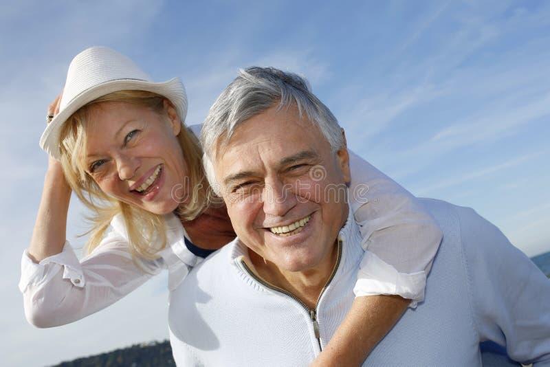 获得快乐的资深的夫妇画象乐趣在一个美好的晴天 库存照片