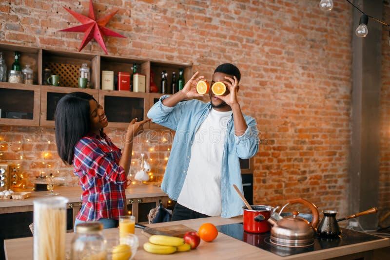 获得快乐的黑的夫妇在厨房的乐趣 库存照片