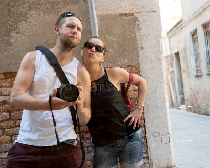 获得性感的凉快的夫妇采取在窗口反射支持的砖墙上的乐趣一selfie 免版税库存照片