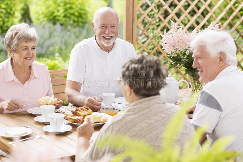 获得愉快和微笑的资深的人民乐趣,当吃breakfas时 免版税库存照片