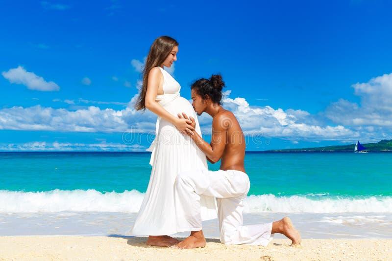 获得愉快和年轻人怀孕的夫妇在一个热带海滩的乐趣 免版税库存照片