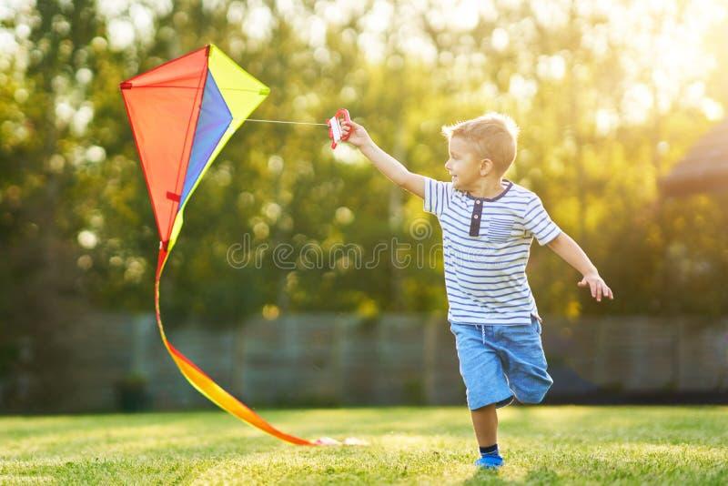 获得愉快的三岁的男孩使用与风筝的乐趣 免版税图库摄影