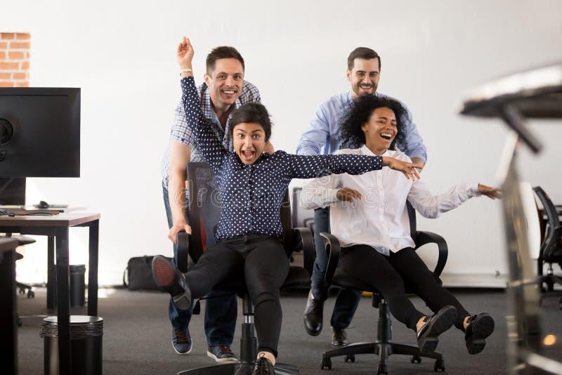 获得愉快的不同种族的办公室的人民乘坐在椅子的乐趣 库存图片