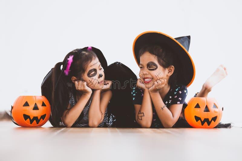 获得愉快的亚裔小孩的女孩在万圣夜庆祝的乐趣 免版税库存照片