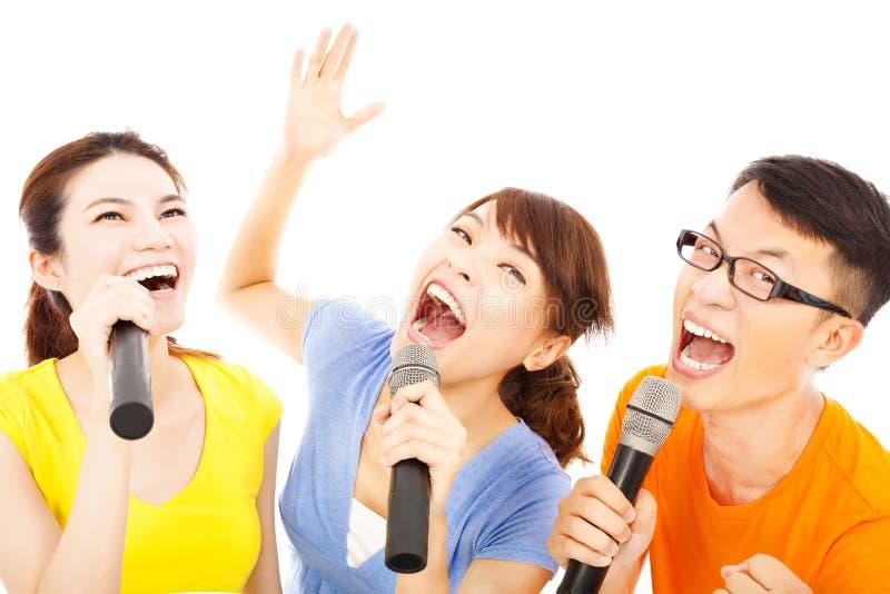 获得愉快的亚洲年轻的小组唱歌与话筒的乐趣 库存照片