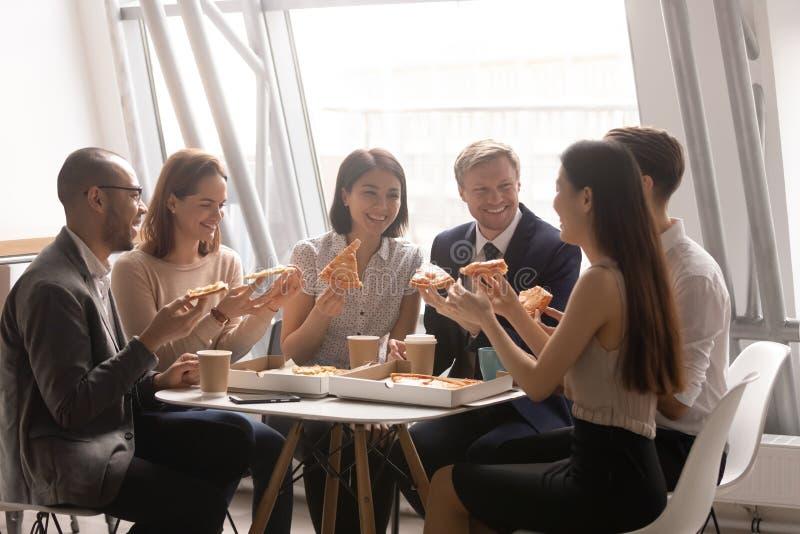 获得愉快的友好的多种族的队一起吃比萨的乐趣 免版税库存照片