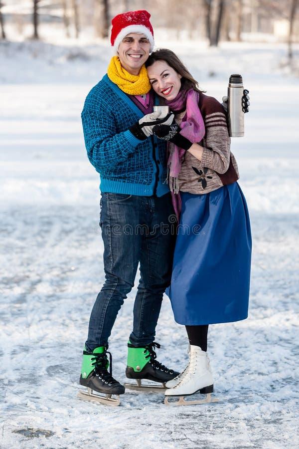 获得愉快的夫妇滑冰和喝从Th的乐趣热的茶 免版税库存图片