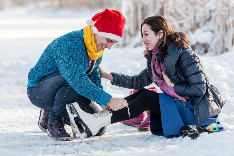 获得愉快的夫妇滑冰在溜冰场的乐趣户外 免版税库存图片