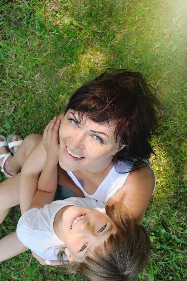 获得愉快的女孩和她的母亲家庭画象在g的乐趣 图库摄影