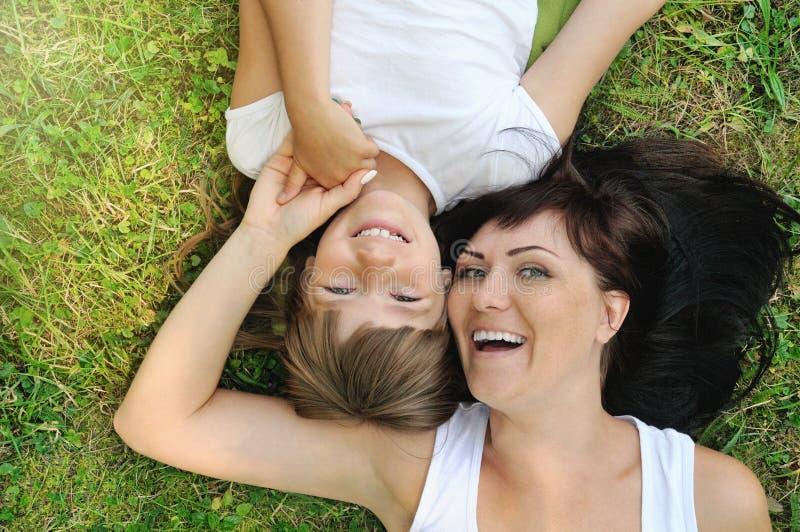 获得愉快的女孩和她的母亲画象在草的乐趣 库存照片
