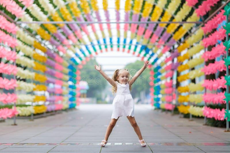 获得愉快的女孩跳跃和在被弄脏的明亮的晴朗的公园胡同的乐趣 愉快的粗心大意的童年概念 免版税库存照片