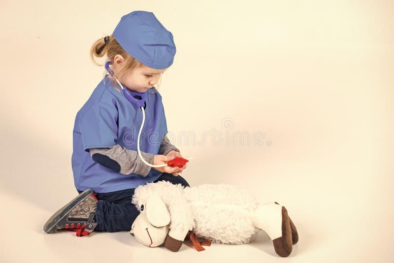 获得愉快的孩子乐趣 医生一致的使用的狩医的小男孩有玩具动物的 库存图片