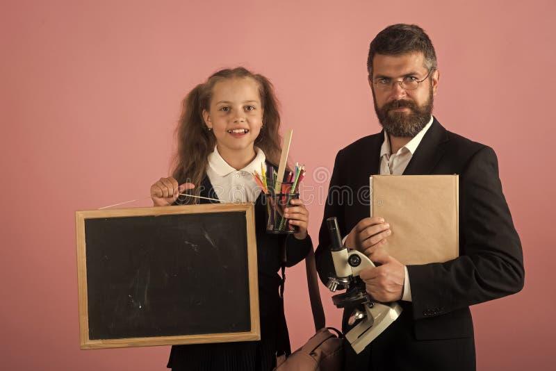 获得愉快的孩子乐趣 教室和选择教育概念 老师和女小学生 免版税图库摄影