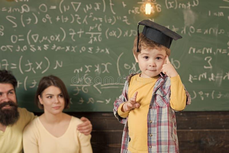 获得愉快的孩子乐趣 神童概念 聪明的孩子,毕业生盖帽的神童指向他的头的 男孩提出 免版税库存图片