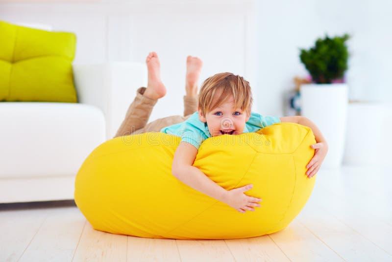 获得愉快的孩子在黄豆袋子的乐趣在家 库存照片