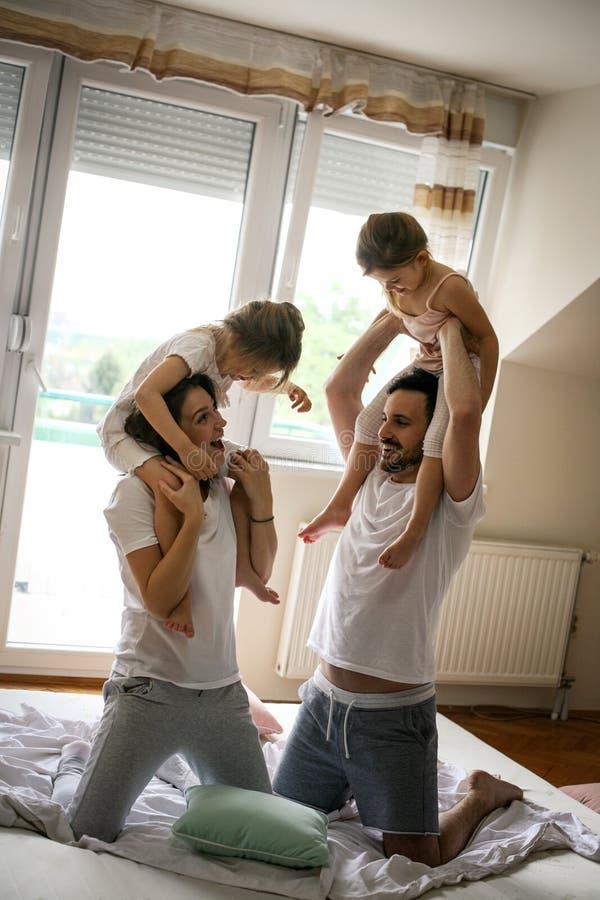 获得愉快的家庭在床上的乐趣 免版税库存照片