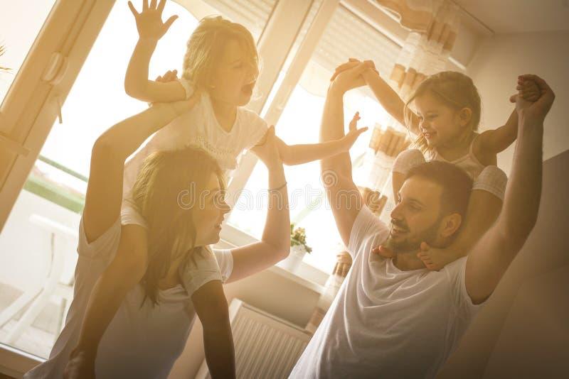 获得愉快的家庭在床上的乐趣 库存照片