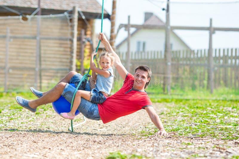 获得愉快的家庭在摇摆的乐趣户外 库存照片