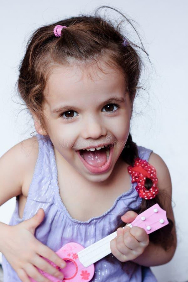 获得愉快的小女孩使用与玩具吉他或尤克里里琴的乐趣 库存图片
